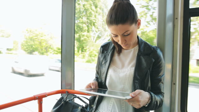 young woman using digital tablet on tram/train. - on the move stock videos & royalty-free footage