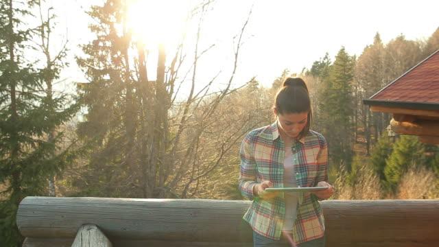 vídeos de stock, filmes e b-roll de mulher jovem com tabuleta digital em férias. - área arborizada