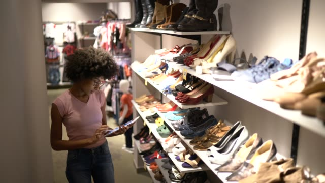 young woman using digital tablet to check invetory at a shoe store - clothes shop stock videos & royalty-free footage