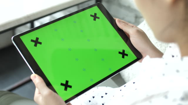young woman using digital tablet with a green screen in landscape mode - e learning stock videos & royalty-free footage
