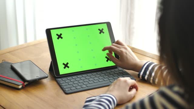 stockvideo's en b-roll-footage met jonge vrouw met behulp van digitale tablet met een groen scherm - tablet pc