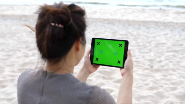 young woman using digital tablet with a green screen,on the beach - equipment stock videos & royalty-free footage