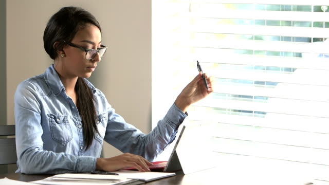 Young woman using digital tablet, working from home
