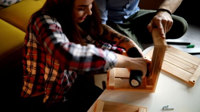 vidéos et rushes de jeune femme à l'aide d'un tournevis électrique d'installation - bricolage