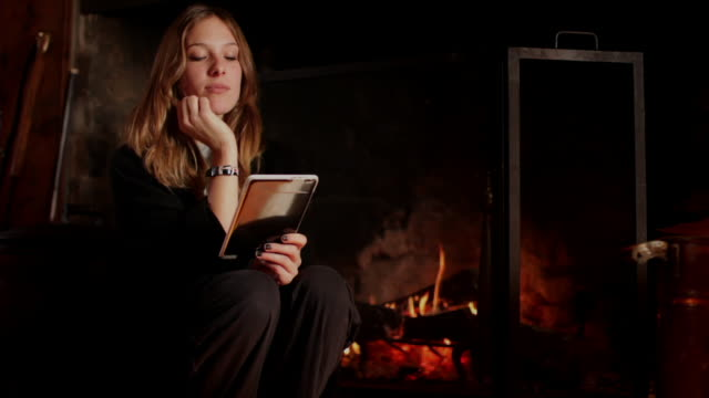 ms young woman using electronic reader, fireplace in background / kingston, new york, usa  - electronic book stock videos & royalty-free footage