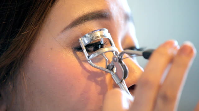 young woman using eyelash curler - curled up stock videos and b-roll footage