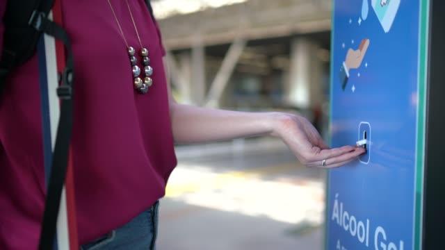 vídeos de stock, filmes e b-roll de jovem usando dispensador de desinfetante para as mãos no aeroporto - travel destinations