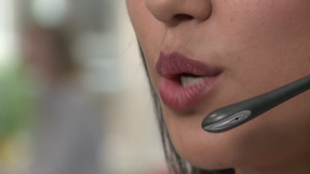 ecu, selective focus, young woman using headset in call center, close-up of mouth - pointer stock videos & royalty-free footage