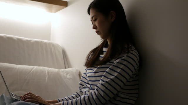 vidéos et rushes de young woman using her computer in bed - crouler sous le travail