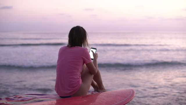 RV MS Young woman using her phone after surfing