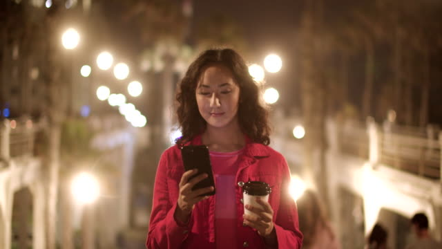 sm ms young woman using her phone and drinking coffee at night - cup stock-videos und b-roll-filmmaterial