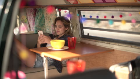 ws young woman using her phone in her camper van - sitting stock videos & royalty-free footage