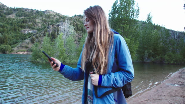 young woman using her phone while hiking in the mountains - exploration stock videos & royalty-free footage