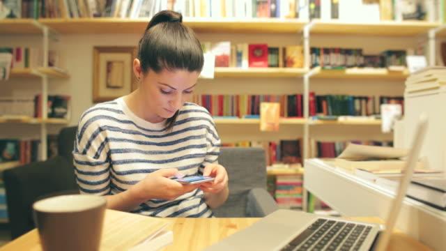 vidéos et rushes de jeune femme se servant de son smartphone dans la bibliothèque. - rayonnage de livre