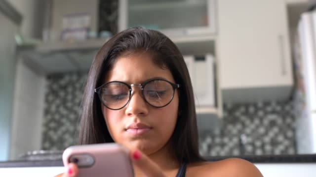 young woman using her smartphone at home - pardo brazilian stock videos & royalty-free footage