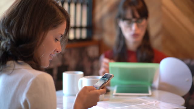 young woman using her smartphone in a coworking space - coffee break stock videos & royalty-free footage