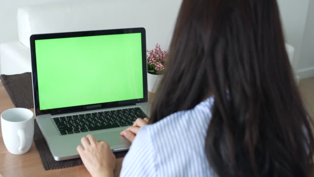Young woman using  Labtop Green Screen at Home