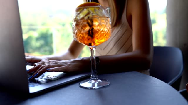 young woman using laptop and drinking aperitif - cocktail stock videos & royalty-free footage