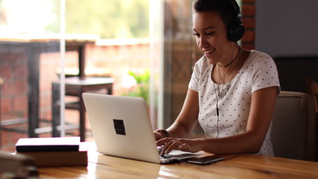 Young woman using laptop and listening music at a cafe