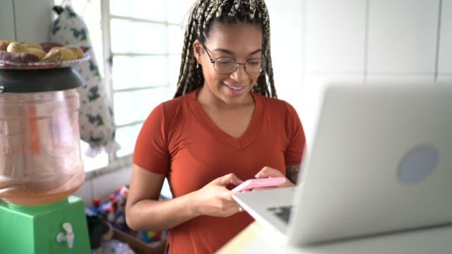 vídeos de stock, filmes e b-roll de jovem usando laptop e celular em casa - 20 anos