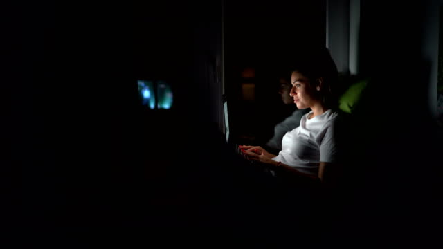 young woman using laptop at home at night - pyjamas stock videos & royalty-free footage