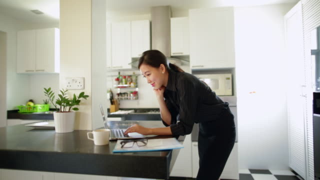 ms young woman using laptop computer in kitchen - working from home stock videos & royalty-free footage