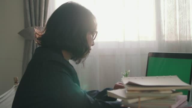 vidéos et rushes de jeune femme à l'aide d'ordinateur portable avec écran vert sur le bureau à la maison - back lit