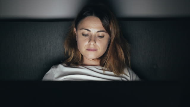 young woman using laptop in bed. - person in further education stock videos & royalty-free footage