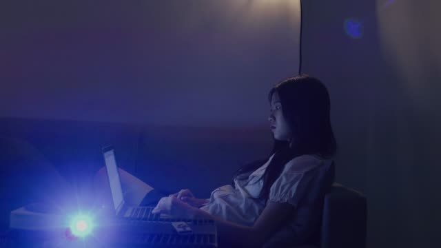 young woman using laptop in darkroom - dunkelkammer stock-videos und b-roll-filmmaterial