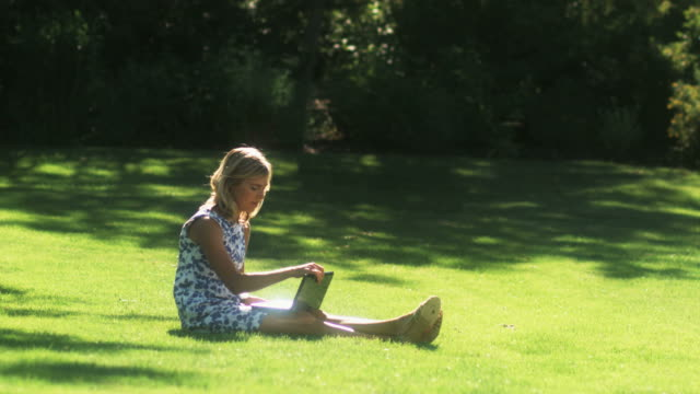 vídeos de stock, filmes e b-roll de slo mo ws young woman using laptop in garden, lehi, utah, usa - lehi
