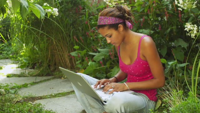 WS Young woman using laptop in garden / Manchester, Vermont, USA