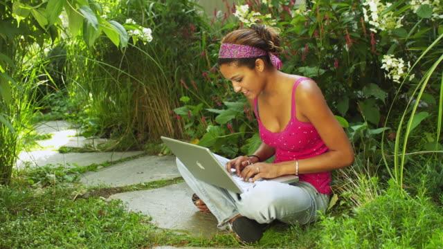 vídeos y material grabado en eventos de stock de ws young woman using laptop in garden / manchester, vermont, usa - cinta de cabeza
