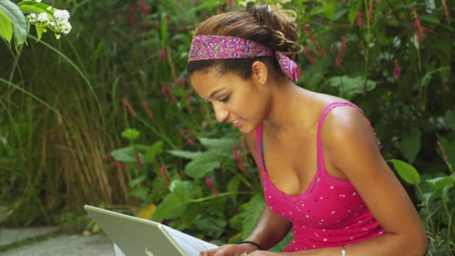 MS Young woman using laptop in garden / Manchester, Vermont, USA