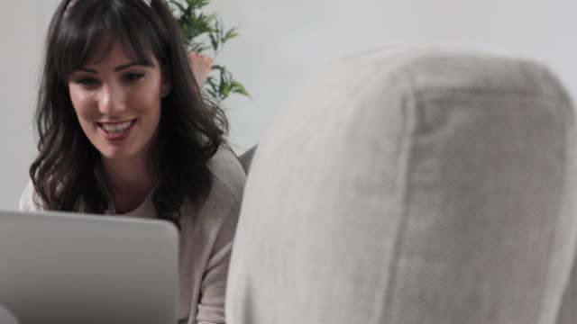 Junge Frau mit Laptop im Wohnzimmer