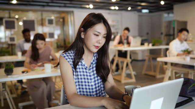 young woman using laptop in open coworking office - white collar worker stock videos & royalty-free footage