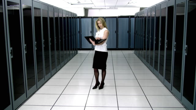 ws young woman using laptop in server room - see other clips from this shoot 1480 stock videos and b-roll footage