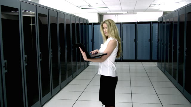 ws ds ms young woman using laptop in server room - see other clips from this shoot 1480 stock videos and b-roll footage