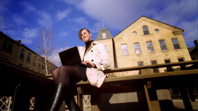 ms young woman using laptop / madison, wisconsin, usa - トレンチコート点の映像素材/bロール