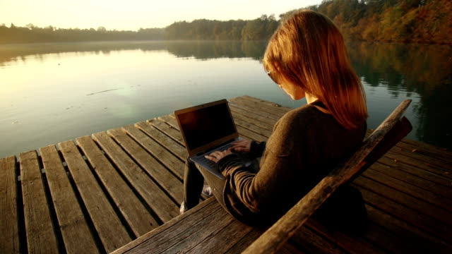 Young woman using laptop on a bench by the lake