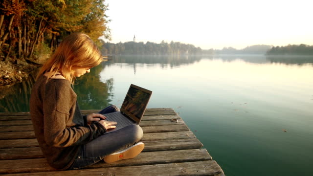 Young woman using laptop on a pier by the lake