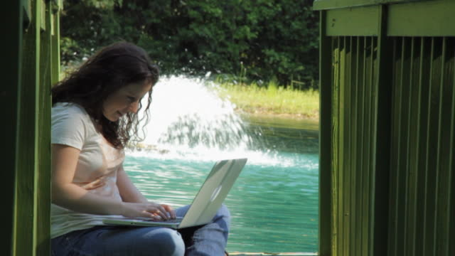 vidéos et rushes de slo mo ms young woman using laptop on jetty, fountain in background / madison, florida, usa - assis en tailleur