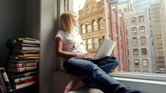 ms, pan, young woman using laptop, sitting on window sill, new york city, new york, usa - anno 2008 video stock e b–roll