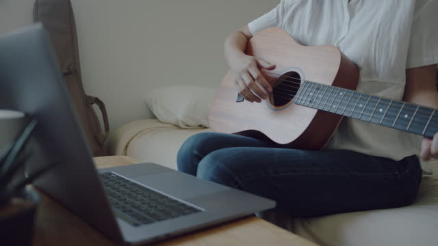 young woman using laptop to video chat while playing acoustic guitar - prevenzione delle malattie video stock e b–roll