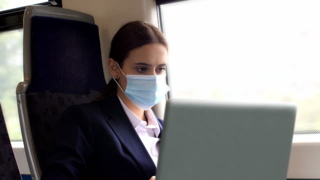 young woman using laptop wearing a mask, working on a train. - train vehicle stock videos & royalty-free footage