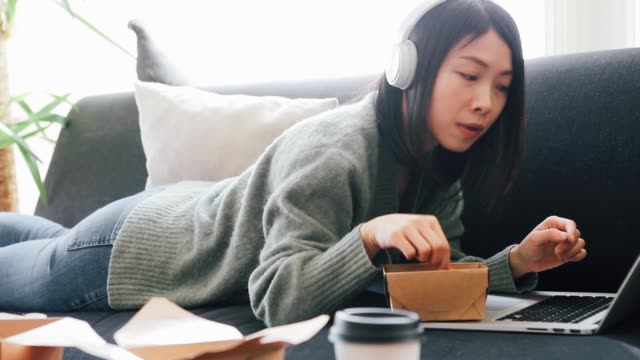 young woman using laptop while having takeaway lunch - home movie点の映像素材/bロール