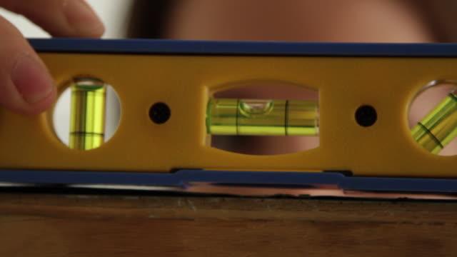 vidéos et rushes de cu young woman using level - mesurer