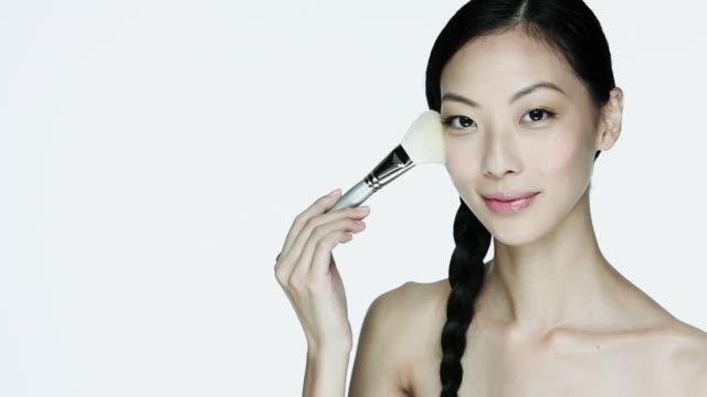 young woman using make up brush on face - フェイスブラシ点の映像素材/bロール