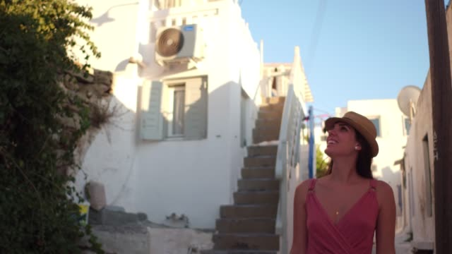 young woman using mobile and walking/exploring greek island - mykonos stock videos & royalty-free footage