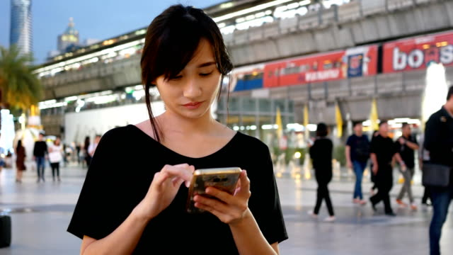 young woman using mobile at night