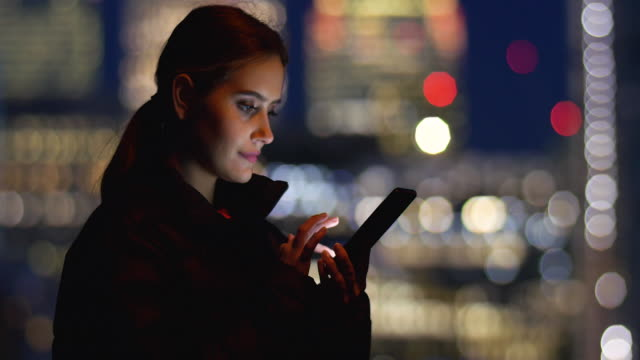 young woman using mobile device in business district at night - telecommunications equipment stock videos & royalty-free footage